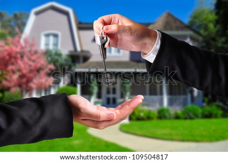 A hand giving a key to another hand. Both persons in suits and a house in the background. - stock photo