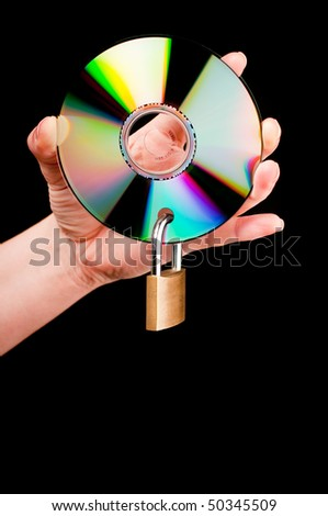 A hand holding a CD with a padlock on black background - stock photo