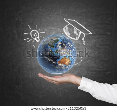 A hand holding a 3d illustration of Earth planet with sketched graduation cap and light bulb. Elements of this image furnished by NASA - stock photo
