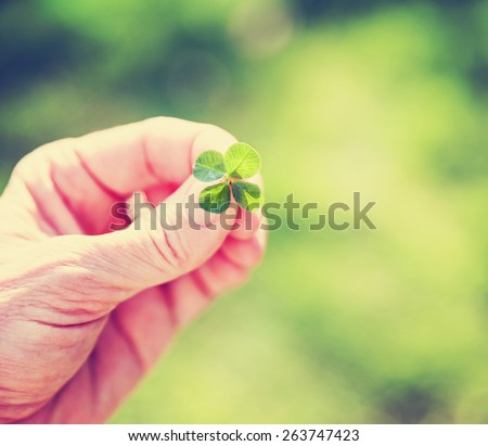 a hand holding a four leaf clover toned with a retro vintage instagram filter (very shallow depth of field) good for luck or st patrick's day  - stock photo