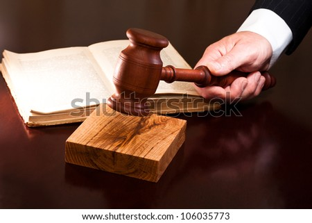 A hand holding a gavel and a book lying on the table - stock photo