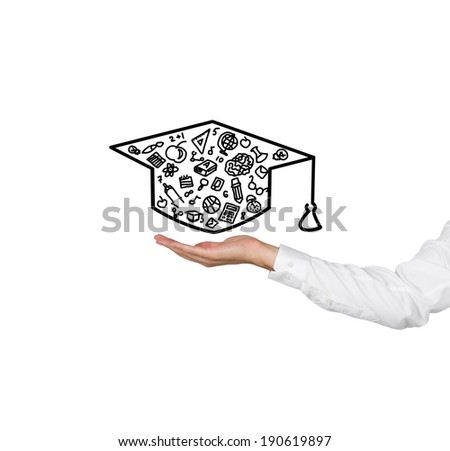 A hand holding a graduation hat. - stock photo