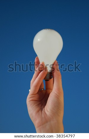 A hand holding a lightbulb against a blue sky - stock photo