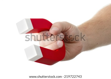 A hand holding a magnet isolated on white to pick up an object - stock photo