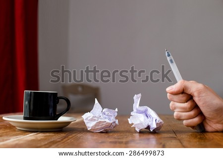 A hand holding a pen writing in his fist, frustrated failure in creativity and work. Crumpled paper coffee cup on a wooden table. - stock photo