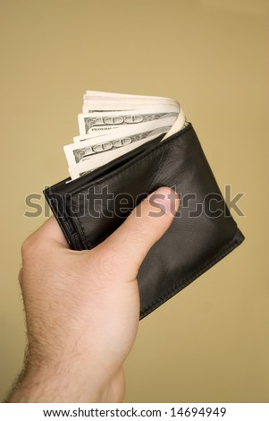 A hand holding a wallet full of cash isolated over a gold background. - stock photo