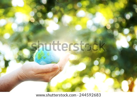 A Hand holding up a small felted world against the sunlight - stock photo