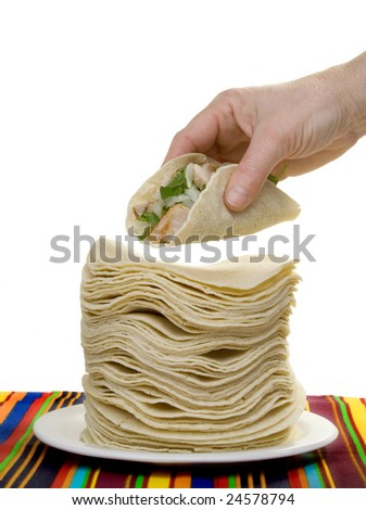 A hand holds a carnitas taco, above a huge stack of corn tortillas. - stock photo