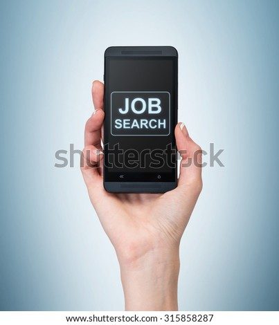A hand holds a fancy smartphone. Words: ' Job search ' on the screen. A concept of recruitment. Light blue background. - stock photo