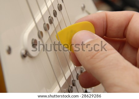 A hand holds a guitar pick and strums an electric guitar. - stock photo