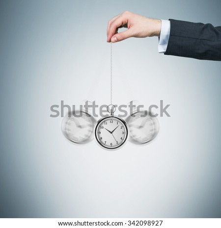 A hand holds a pocket watch in a chain as a pendulum. Light blue background. Time is money concept. - stock photo