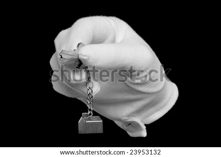 A hand in a white glove holding the key to a new house, isolated on black. - stock photo