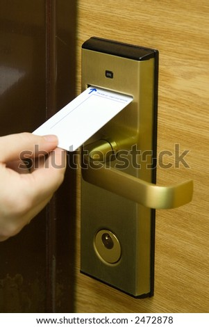 A hand inserting keycard in the electronic lock - stock photo