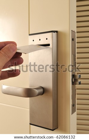 A hand inserting keycard in the electronic lock - a series of HOTEL images. - stock photo