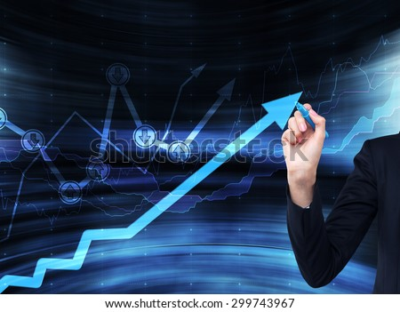 A hand is drawing a growing arrow on the glass scree, Blue dark background with financial graphs. - stock photo