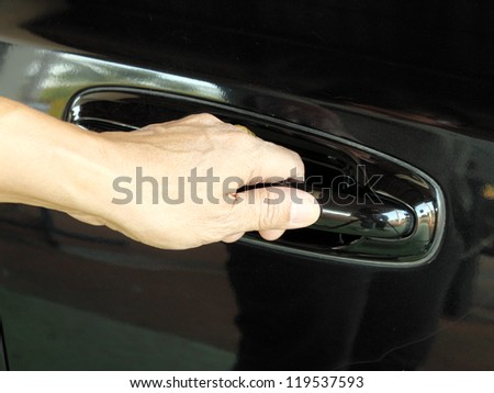 a hand is going to pull a car's door handle - stock photo