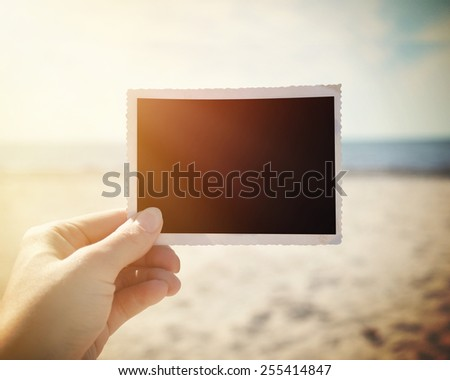 A hand is holding up a blank photo snapshot at a sunny beach to add your own photo or message in the area. - stock photo