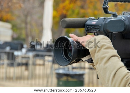 A hand is operating a tv camera - stock photo