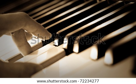 A hand of a boy playing piano - stock photo