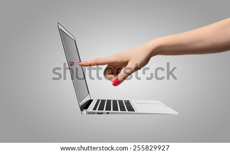 A hand of a woman touches the screen of the notebook - stock photo