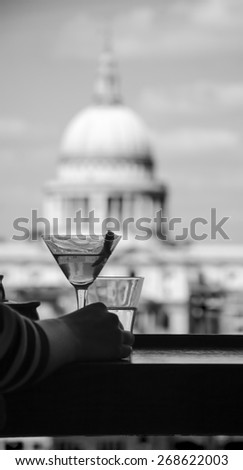 A hand of a woman with refreshing cocktail in martini glass with lemon twist and a digital tablet against a view from Tate Modern gallery's cafe on St Paul Cathedral. London, England. Black and white. - stock photo