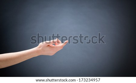 A hand of a young woman stretching out in a gentle position about to touch something with the fingertip of the index finger. - stock photo