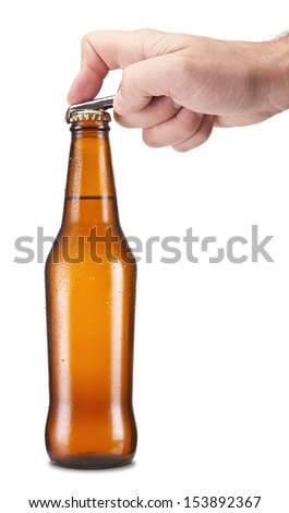 A hand opening a bottle of beer. - stock photo