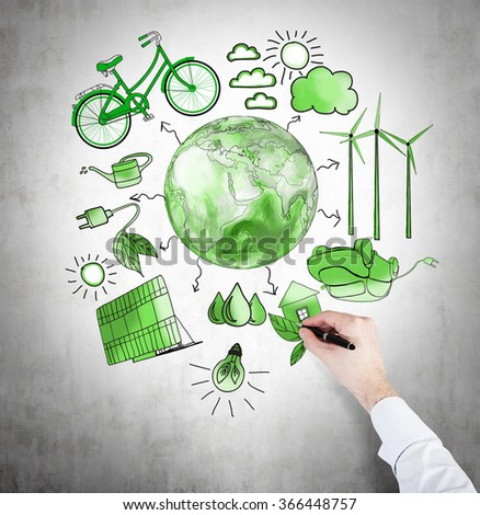 A hand painting symbols of alternative energy sources painted in green colours on a concrete wall. Green Earth in the middle. Concept of clean environment. - stock photo