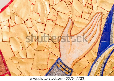 A hand raised in prayer pointed upwards- detail of a mosaic of a saint, with copy space for text - stock photo