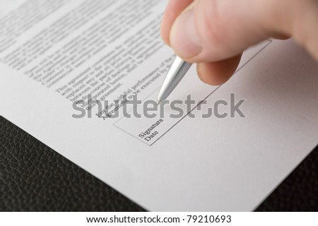 A hand signing a contract - stock photo