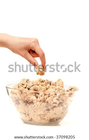 A hand sneaking a taste test of cookie dough. - stock photo