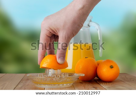 A hand squeezing juice from an orange on a manual glass squeezer.  Set on a wooden planked table with a group of three oranges and a glass jug of juice.  Outdoor background of soft foliage. - stock photo
