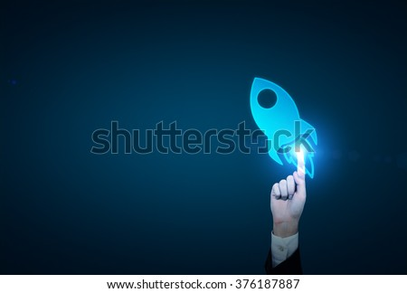 A hand touching a blue image of a rocket so that it is activated. Dark blue backgroud. Concept of launching a new project. - stock photo