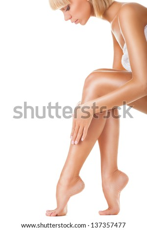 A hand touching beautiful woman's legs isolated on white background - stock photo