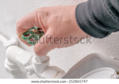 A hand turning the stopcock valve of a water heating system - stock photo