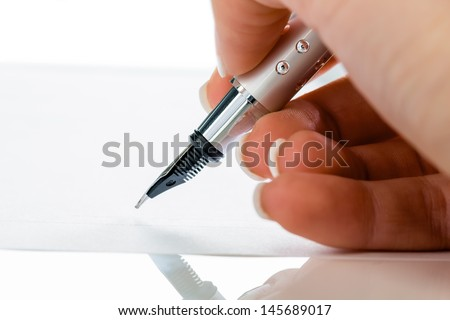 a hand with a fountain pen in the untrerschrift under a contract or testament. - stock photo
