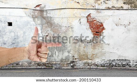 A hand with a pointing finger in a desolated back lane.  - stock photo