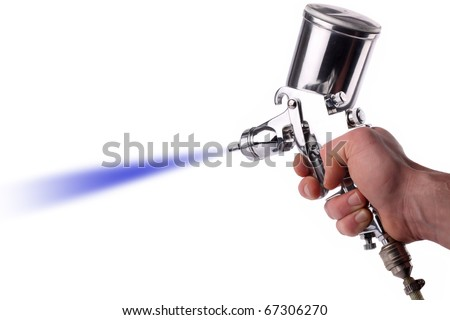 A hand with a spray gun at work. - stock photo