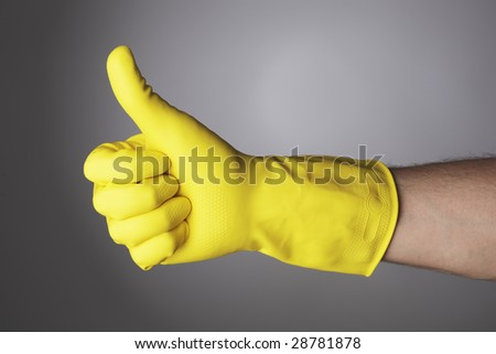 A Hand with yellow protective glove doing a thumb up sign - stock photo