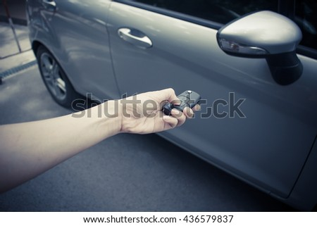A hand women holding a car's remote control pointing to the door - stock photo