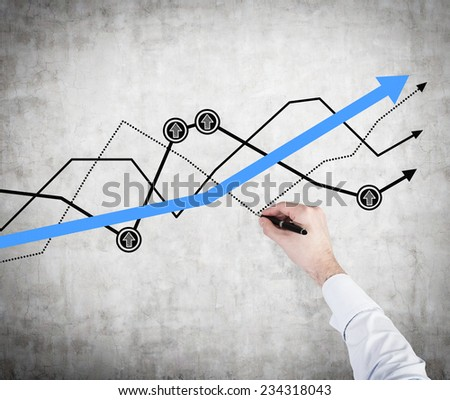 A hand writing a chart on the concrete wall. - stock photo