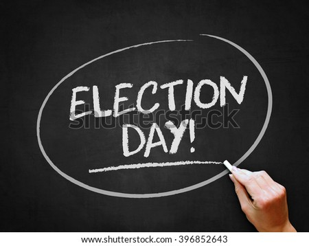 A hand writing 'Election Day!' on chalkboard. - stock photo