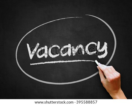 A hand writing 'Vacancy' on chalkboard. - stock photo