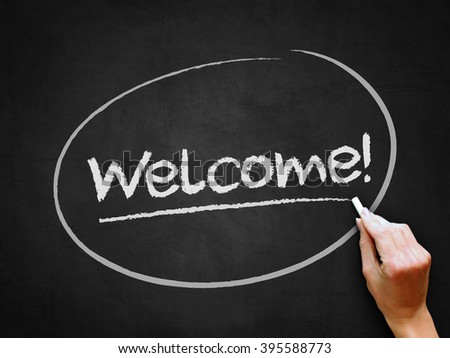A hand writing 'Welcome!' on chalkboard. - stock photo