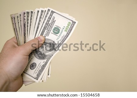 A handful of cash isolated over a gold background. - stock photo