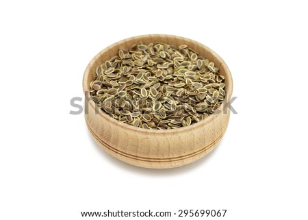 a handful of dried fennel seeds in a wooden bowl on a white background - stock photo