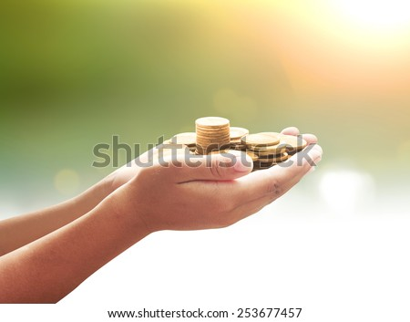 A handful of golden coins in the palm of a hand over blurred the city beautiful sunset background. Money coin, Investment, Insurance Agent, Banking, Saving, Trust, Planing, Management, Cash concept. - stock photo