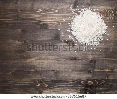 a handful of rice on a wooden background border,with text area - stock photo