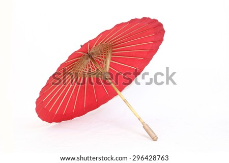 A handmade red, Asian parasol or umbrella isolated - stock photo