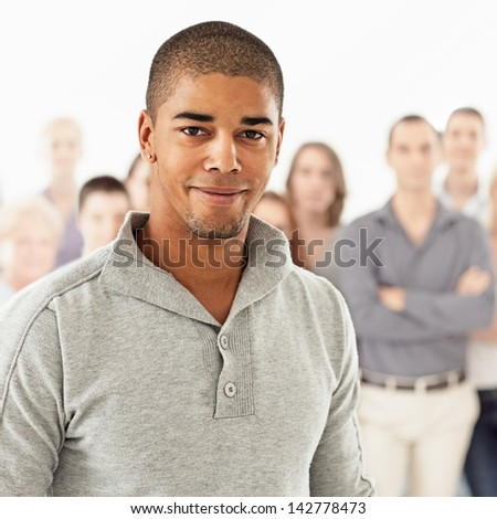 A handsome African-American man posing in front of a group of people. - stock photo